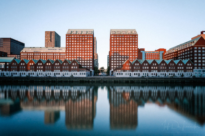 The rising sun accentuates the red brick of the buildings in Rotterdam harbor inlet.